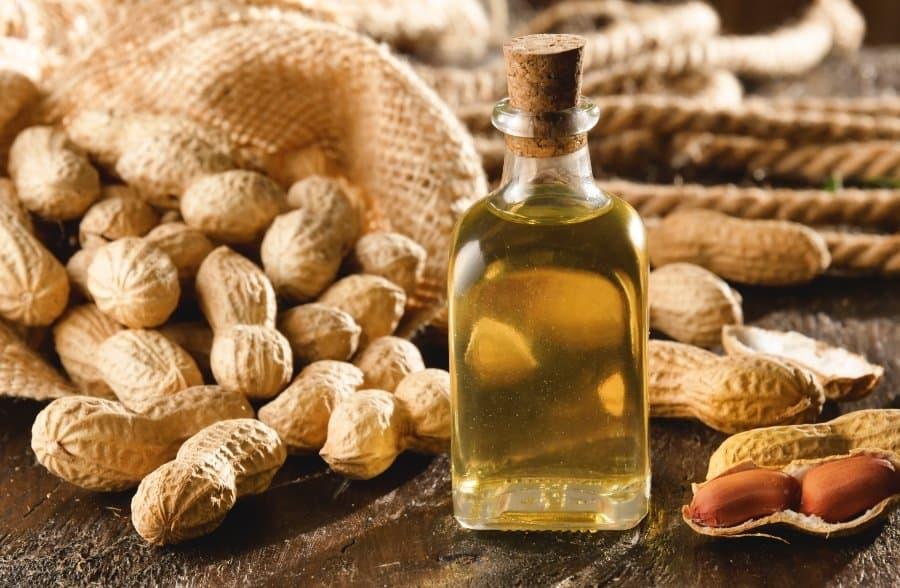jar of peanut oil and shelled peanuts